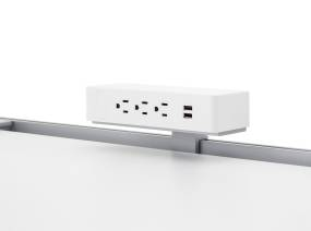 White 3 Outlet USB Powerstrip Rail Mount on top of a white desk.