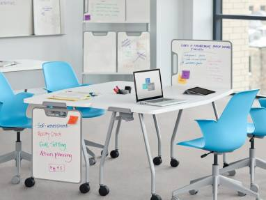 Two white Verb Tables next top each other with four blue Node chairs