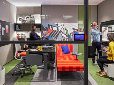 Three people work together in an office enclave furnished with Turnstone Buoy seating, Steelcase Think stools, and a Steelcase Ology bench Steelcase Room Wizard is seen next to the door