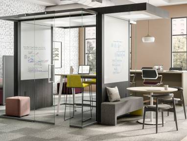 Open space with an Irys Pod with glass walls, whiteboard on a wall, green stools and a high wooden table.
