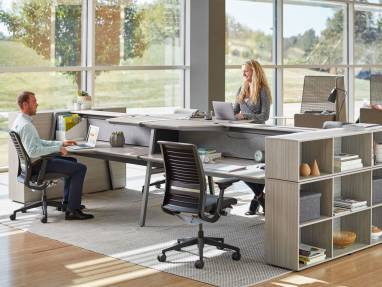 Two people work at a Bivi Dual Height workstation. Steelcase Think desk chairs and Bivi Depot shelving are also pictured.