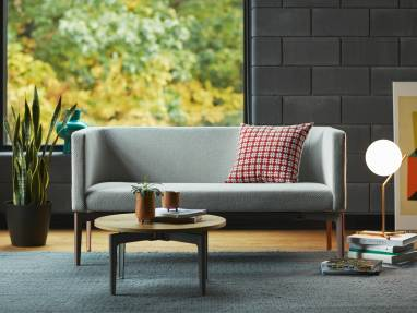 A Bivi Rumble Seat sofa is seen upholstered in gray material with a red and white throw pillow sitting near one end In front of the sofa is a round Bassline occasional table