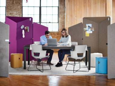 2 people collaborating in the office with surrounding privacy screens