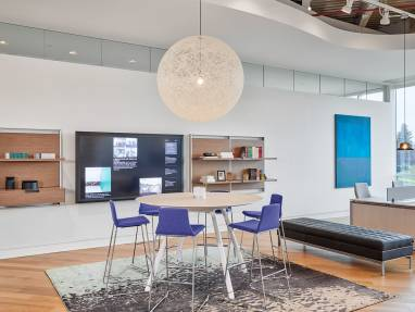 A group of Montara650 stools are arranged around a Potrero415 table. Nearby, a group of workstations have Gesture desk chairs by Steelcase next to them.