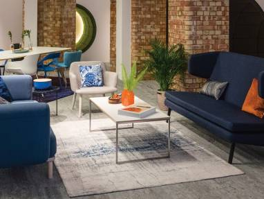 Two Bolia lounge sofas in different shades of blue face each other in a lounge setting with a beige chair nearby and a white table in the center