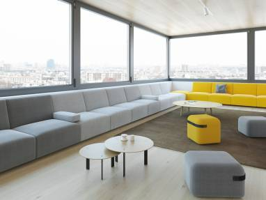 Grey, white and yellow Viccarbe seating is placed along a wall in an office lounge, along with benches and tables