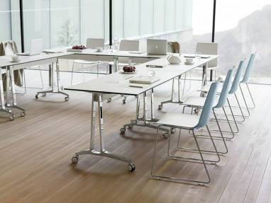 A group of chairs designed by Wiesner-Hager arranged around tables with casters in a conference room
