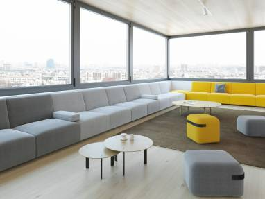 modular lounge sofa in gray and yellow upholstery lining the walls of an open office space