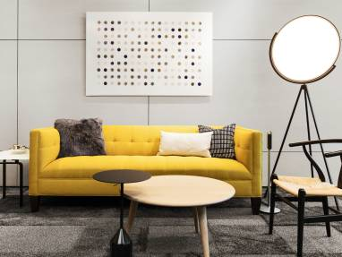 A yellow sofa in a lounge area with a Wishbone chair from Coalesse and Superloon lamp from FLOS next to it