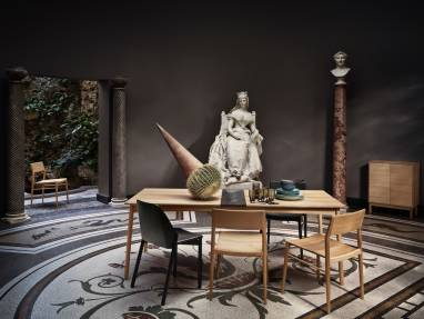 A Bolia Meet dining table is shown in the middle of a room with some chairs next to it