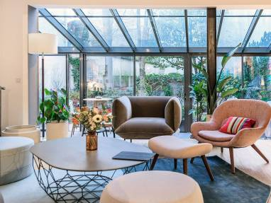 Bolia Steelcase products are shown in a lounge setting with a Comb round coffee table in the center of the space and a Cloud armchair and Philippa armchair next to it