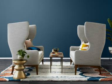 two large tufted gray sofas with a slim coffee table between them