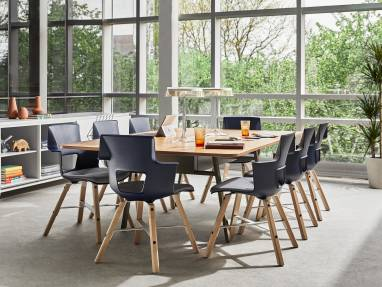 An office meeting area near a window features a collection of Shortcut Wood chairs from Turnstone are arranged around a table. The chairs have a dark blue seat and wooden legs.