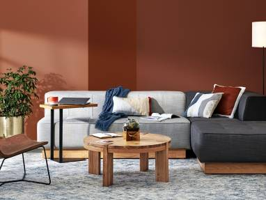 A collection of West Elm Work products in a lounge setting, including a Conover Plinth armless sofa, Conover Plinth ottoman, Boerum coffee table, Slope lounge chair, and Linear C-Table