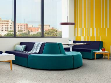 A Bassline lounge system with blue and green upholstery in a lounge area with a Bassline Asymmetrical side table next to a sofa