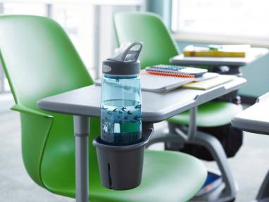 A water bottle is placed in the cupholder attached to the worksurface of a green Node tripod-base chair