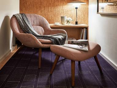 A Philippa armchair, part of the Steelcase + Bolia partnership is, shown in an ancillary office space with a matching footrest