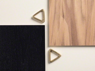 Brass triangles placed next to samples of black wood and natural wood material samples
