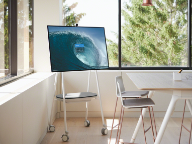 A screen is displayed on a Steelcase Roam mobile stand next to a Potrero415 table and Montara seating