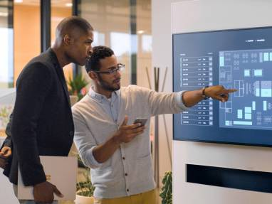 team member pointing at a display monitor showing Steelcase Live Map while discussing with a colleague