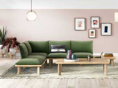 A West Elm Work Boardwalk lounge sofa with green cushions around a West Elm Work Boardwalk rectangular coffee table