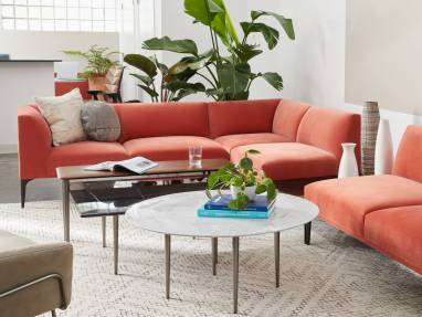 A West Elm Work Mesa sectional sofa with orange upholstery shown with West Elm Work tables in an office lounge setting