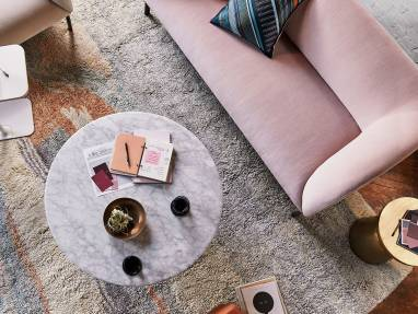 An overhead view of an office lounge that features a selection of products from the Steelcase West Elm partnership, including a pink Billow lowback sofa, a cream Billow lounge chair, Martini side table, and Horizon Nesting Table