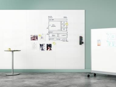 A very large whiteboard on a wall, next to it there is a mobile whiteboard.