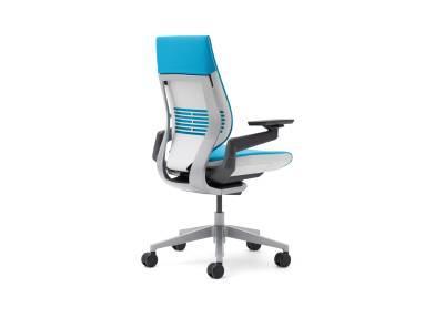 A blue, wrapped-back gesture chair from the back with the seat facing the right