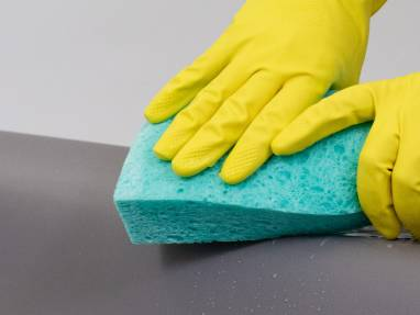 image showing gloved hand using sponge to clean product