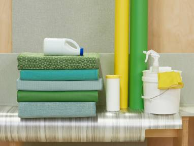 stack of fabrics with bleach bottle, bucket and spray bottle