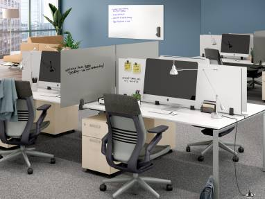 Office space with PolyVision Boundri™ screen dividers between individual workstations, black Gesture chairs and white desks.