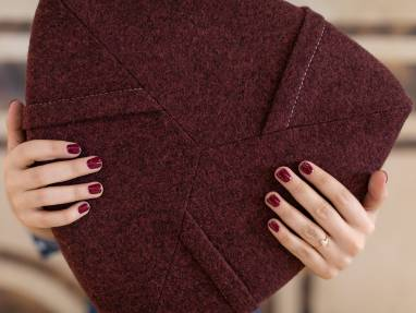 A woman's hands with burgundy-painted nails holding a burgundy Turnstone Campfire Pouf.