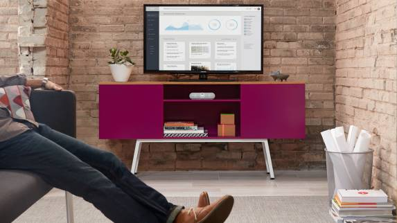 A person relaxes on a sofa next to a pink-colored Bivi Trunk with a monitor placed on top of it