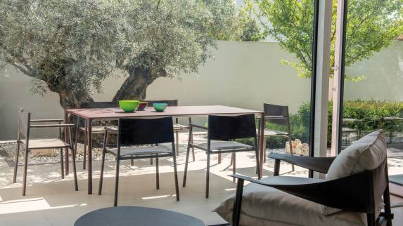 Rectangular table and Emu Terramare Seating outside in a yard.
