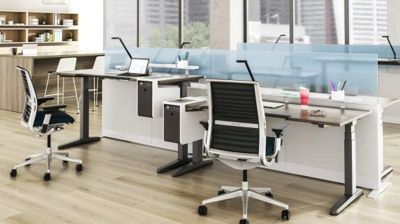 SOTO Personal Consoles on height-adjustable desks in an open office