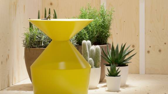 A yellow Shape table from the Viccarbe Imports Collection with a collection of cactus plants in the background