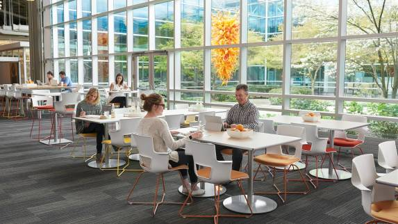 Shortcut X-base chairs with orange and yellow legs are placed around Steelcase Groupwork tables in an office cafe