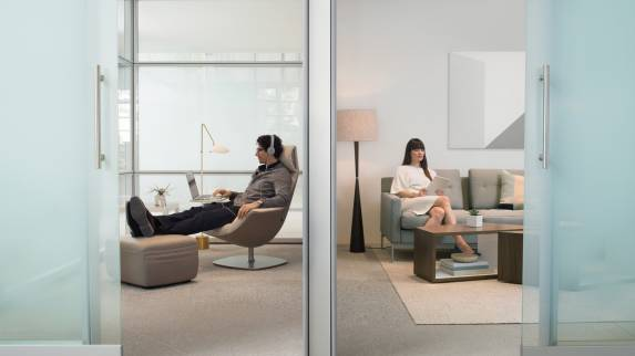 A man wearing headphones works on a laptop while using a Massaud Work Lounge in a private enclave while a woman sits on a Millbrae Lifestyle sofa in a neighboring enclave
