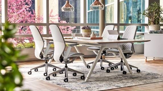 Four SILQ desk chairs with gray upholstery are arranged around a Potrero415 table in a collaborative space near a window