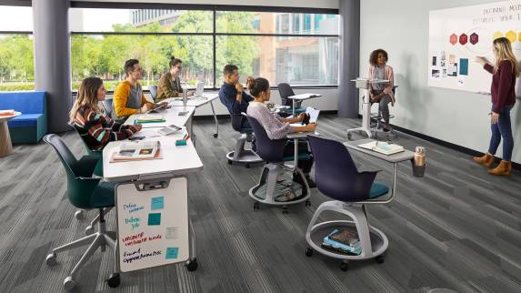 A group of students in a classroom sits in Node tripod base chairs and Node 5-star base chairs while a person at a whiteboard teaches