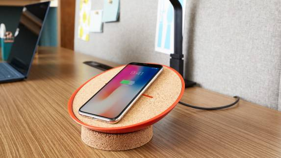 A phone charges on a SOTO wireless charger placed on a desk