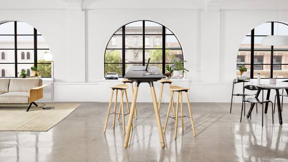 A Potrero415 Light table with wood legs and black top and Enea Cafe wood stools around it