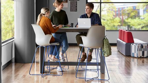 Higher education students gather around the slim table in Node X base chairs in an in-between space environment.