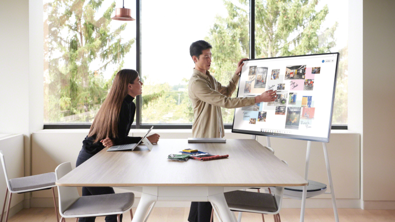 A man presents information at a Steelcase Roam while a woman listens while standing next to a Potrero415 table with Montara650 stools