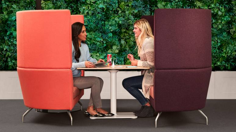 Two people sit in a collaborative space with Aspect booths by Orangebox.
