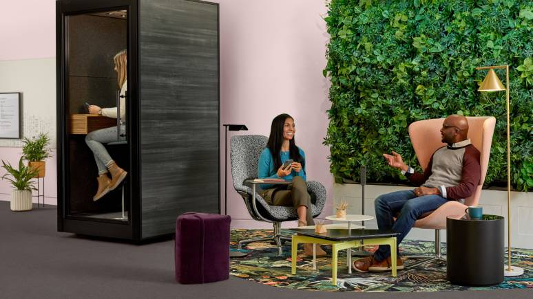 Two people chat in an open collaboration space furnished with Turnstone and Coalesse products.