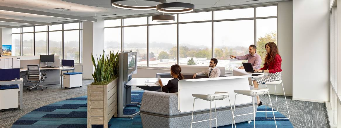 People gather in a Steelcase media:scape lounge with Scoop stools