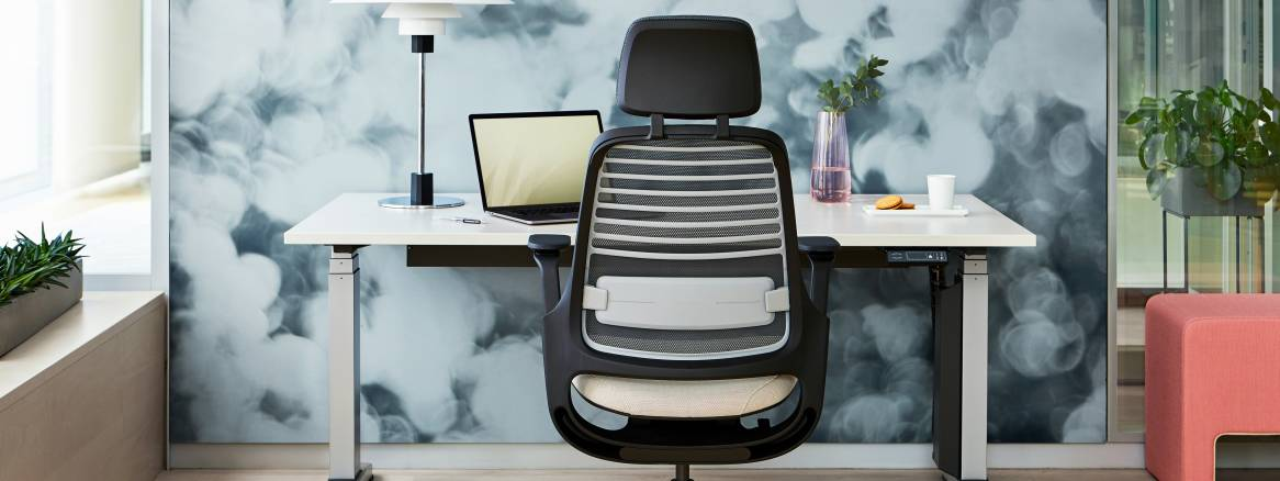 Black Steelcase Series 1 with headrest sitting in front of a white height-adjustable desk.
