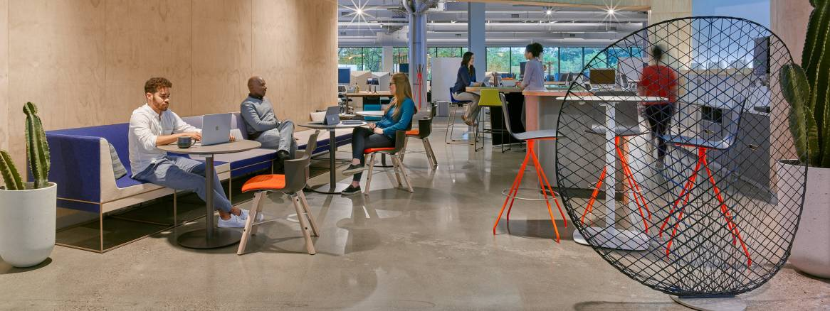 People work in an office lounge while using Umami lounge seating and Shortcut Wood chairs. Viccarbe Klip stools are also pictured.
